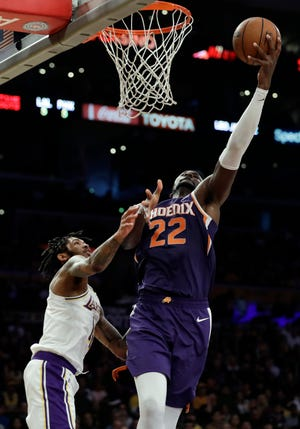Deandre Ayton drives past Lakers forward Brandon Ingram during the first half of a game Dec. 2 at Staples Center.