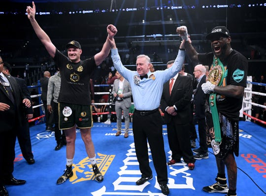 Tyson Fury and Deontay Wilder pose for a photo with referee Jack Reiss after fighting to a draw in their World Boxing Council heavyweight tile fight Dec. 1 at Staples Center,