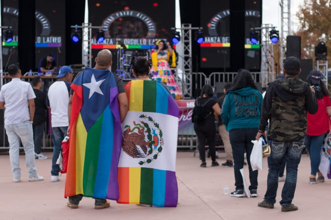 Jonathan Cruz and Luis Arias watch a performance at the Latino Pride Festival while wearing pride versions of the Puerto Rico and Mexico flag on Dec. 1.
