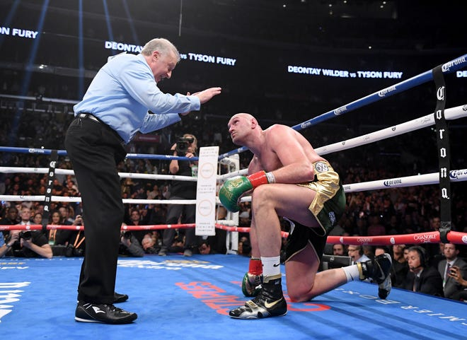 Tyson Fury looks up as he receives a count from referee Jack Reiss in the ninth round of his heavyweight title fight with Deontay Wilder on Dec. 1 at Staples Center.