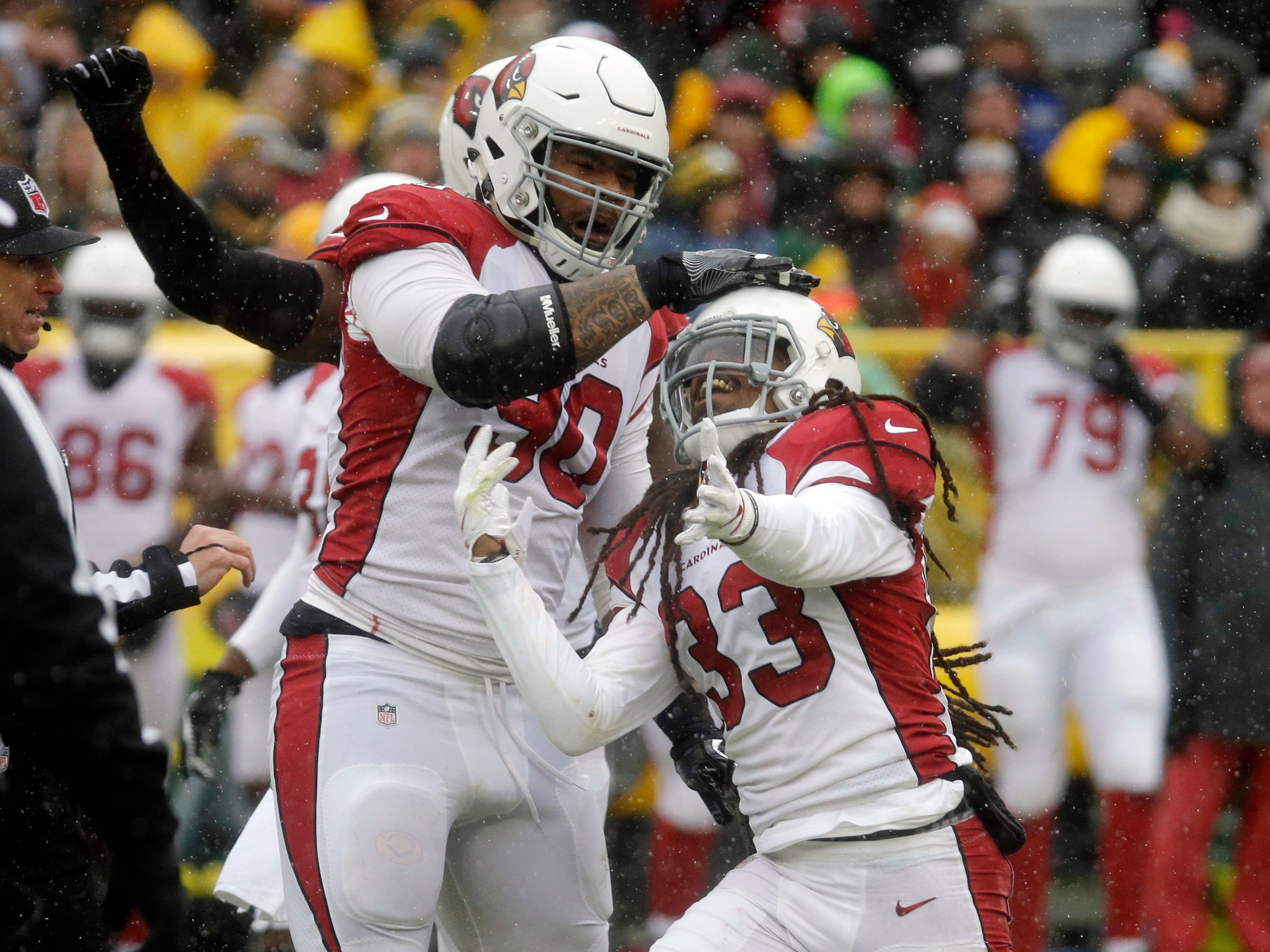 Arizona Cardinals defensive back Tre Boston (33) and defensive tackle Robert Nkemdiche (90) celebrate after a play against the Green Bay Packers during the first half of an NFL football game Sunday, Dec. 2, 2018, in Green Bay, Wis. (AP Photo/Mike Roemer)