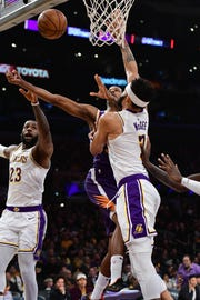 Suns forward Trevor Ariza puts up a shot between Lakers forward LeBron James and center JaVale McGee during the first quarter of a game Dec. 2 at Staples Center.
