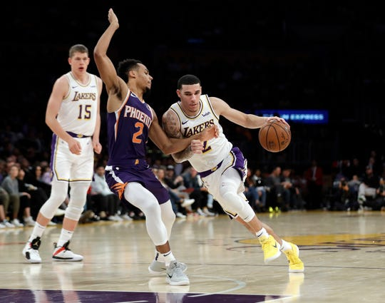 Los Angeles Lakers' Lonzo Ball, right, is defended by Phoenix Suns' Elie Okobo (2) during the second half of an NBA basketball game Sunday, Dec. 2, 2018, in Los Angeles. (AP Photo/Marcio Jose Sanchez)