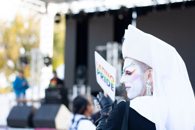 An attendee at the Latino Pride Festival at Corona Ranch in Phoenix holds a Latino Pride sign as they wait for performers to take the stage on Dec. 1.