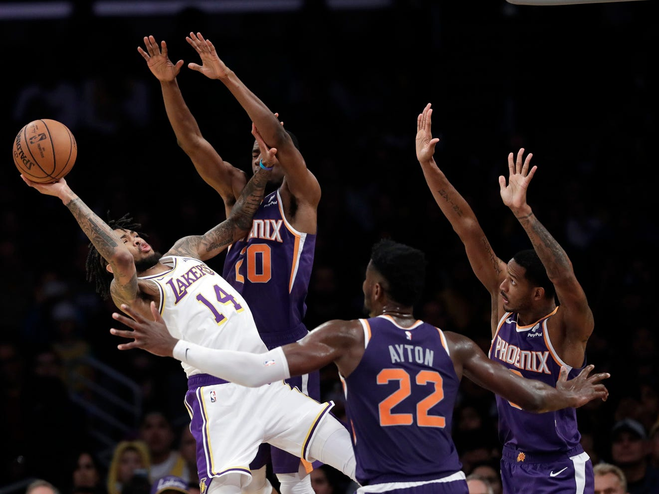 Los Angeles Lakers' Brandon Ingram (14) attempts a shot as Phoenix Suns' Josh Jackson, second from left, Deandre Ayton (22) and Trevor Ariza, right, defend during the first half of an NBA basketball game Sunday, Dec. 2, 2018, in Los Angeles. (AP Photo/Marcio Jose Sanchez)