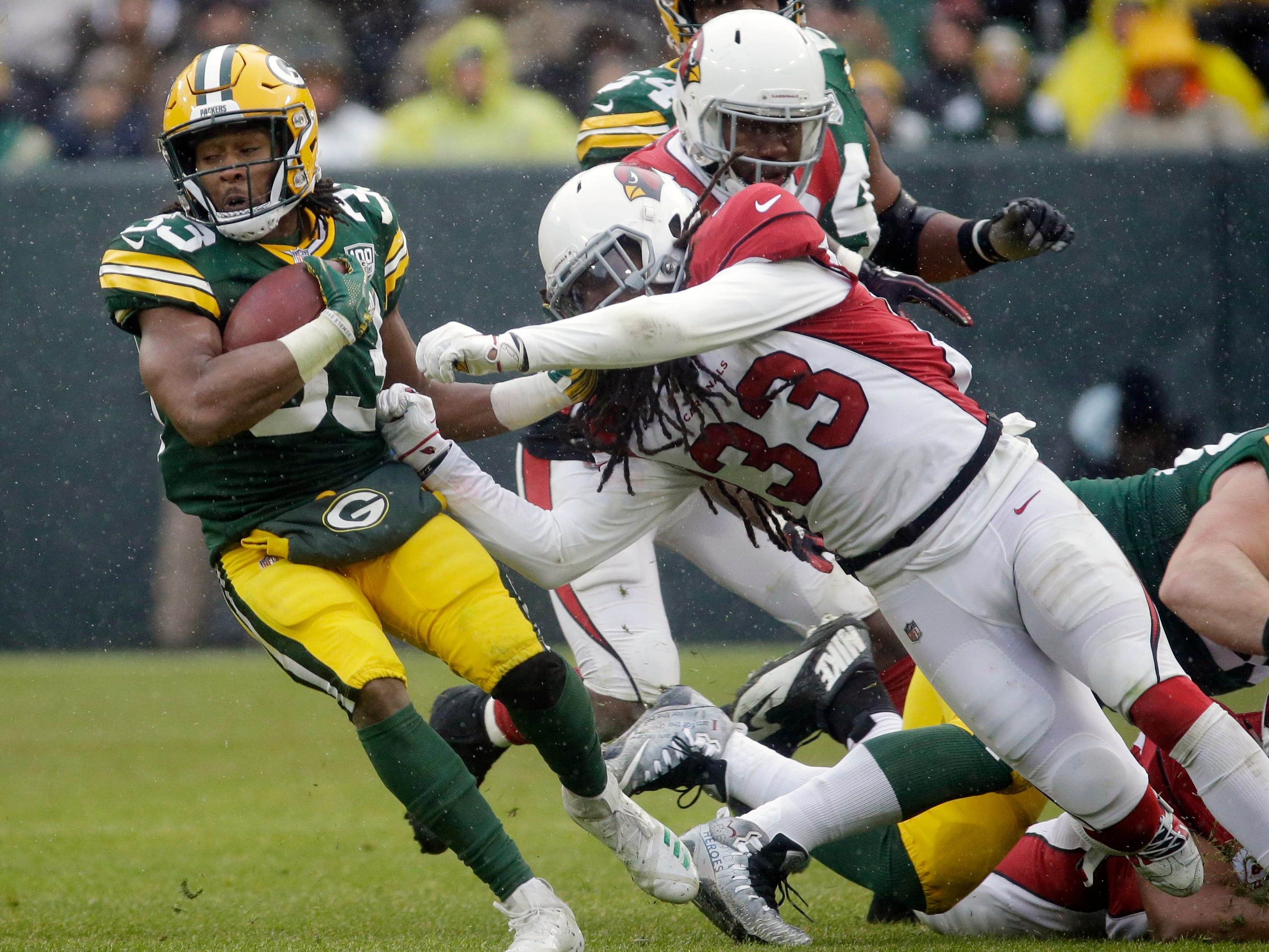 Green Bay Packers running back Aaron Jones is hit during a run by Arizona Cardinals defensive back Tre Boston during the second half of an NFL football game Sunday, Dec. 2, 2018, in Green Bay, Wis. (AP Photo/Mike Roemer)