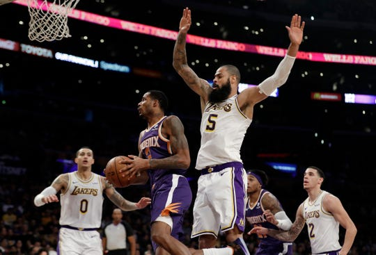 Suns forward Trevor Ariza drives past Lakers center Tyson Chandler during the first half of a game Dec. 2 at Staples Center.