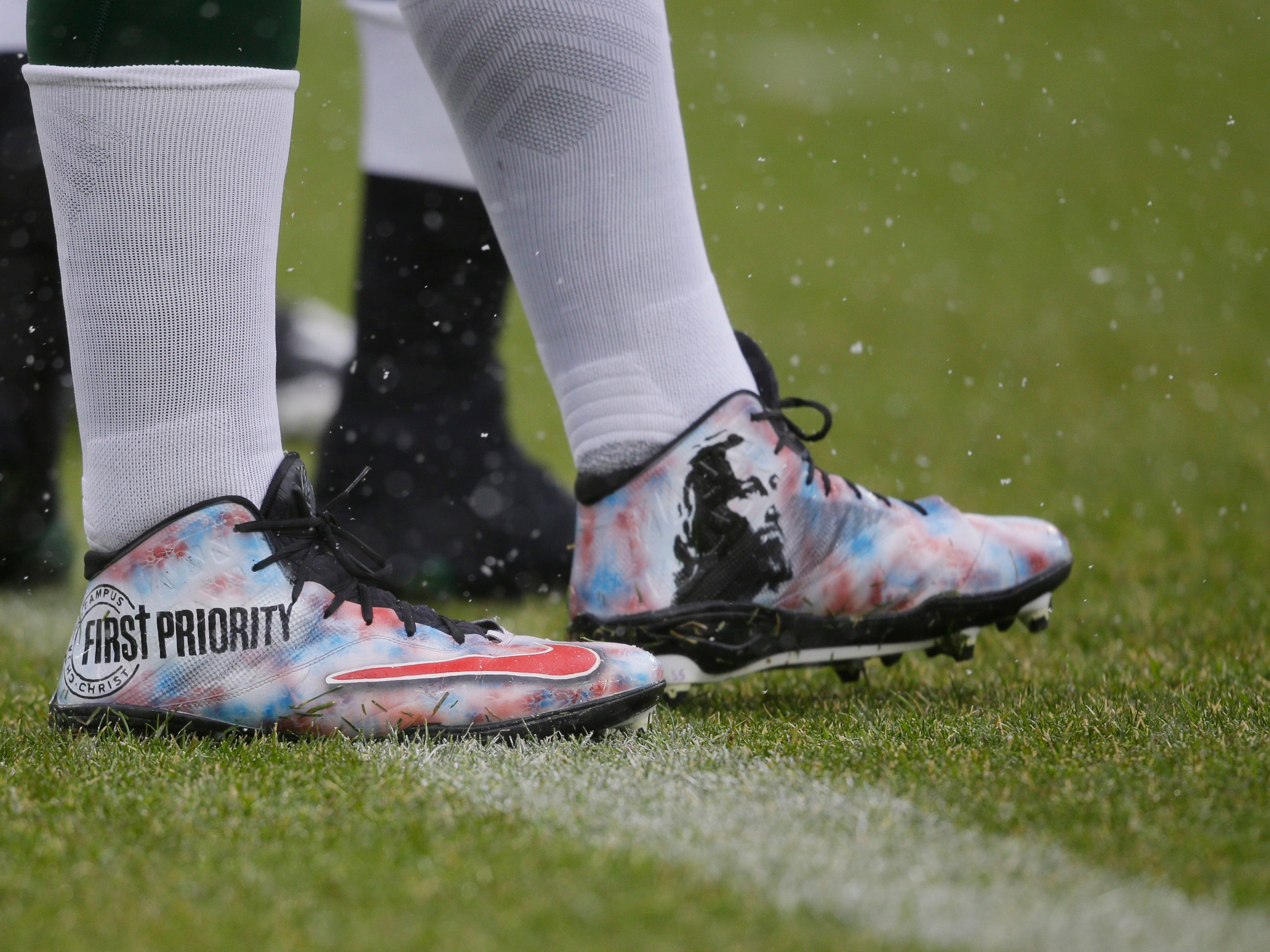 Green Bay Packers offensive guard Lucas Patrick wears custom cleats in warm ups before an NFL football game between the Green Bay Packers and the Arizona Cardinals Sunday, Dec. 2, 2018, in Green Bay, Wis. (AP Photo/Jeffrey Phelps)