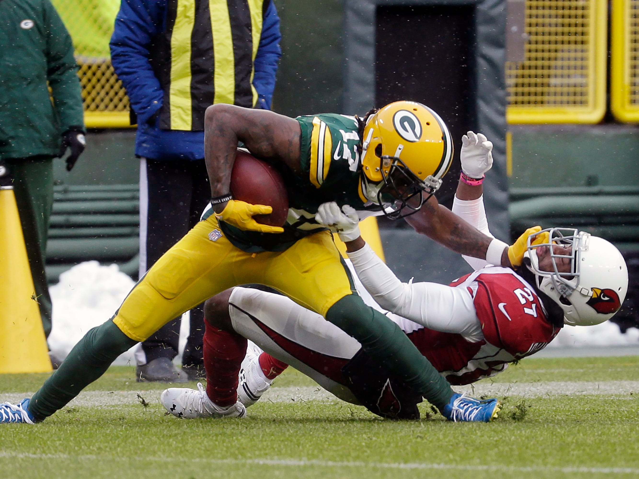 Green Bay Packers wide receiver Davante Adams, left, is hit by Arizona Cardinals defensive back Leonard Johnson, right,  after making a catch during the first half of an NFL football game Sunday, Dec. 2, 2018, in Green Bay, Wis. (AP Photo/Mike Roemer)