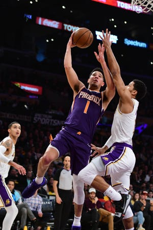 Suns guard Devin Booker puts up a shot against Lakers guard Josh Hart during the second quarter of a game Dec. 2 at Staples Center.