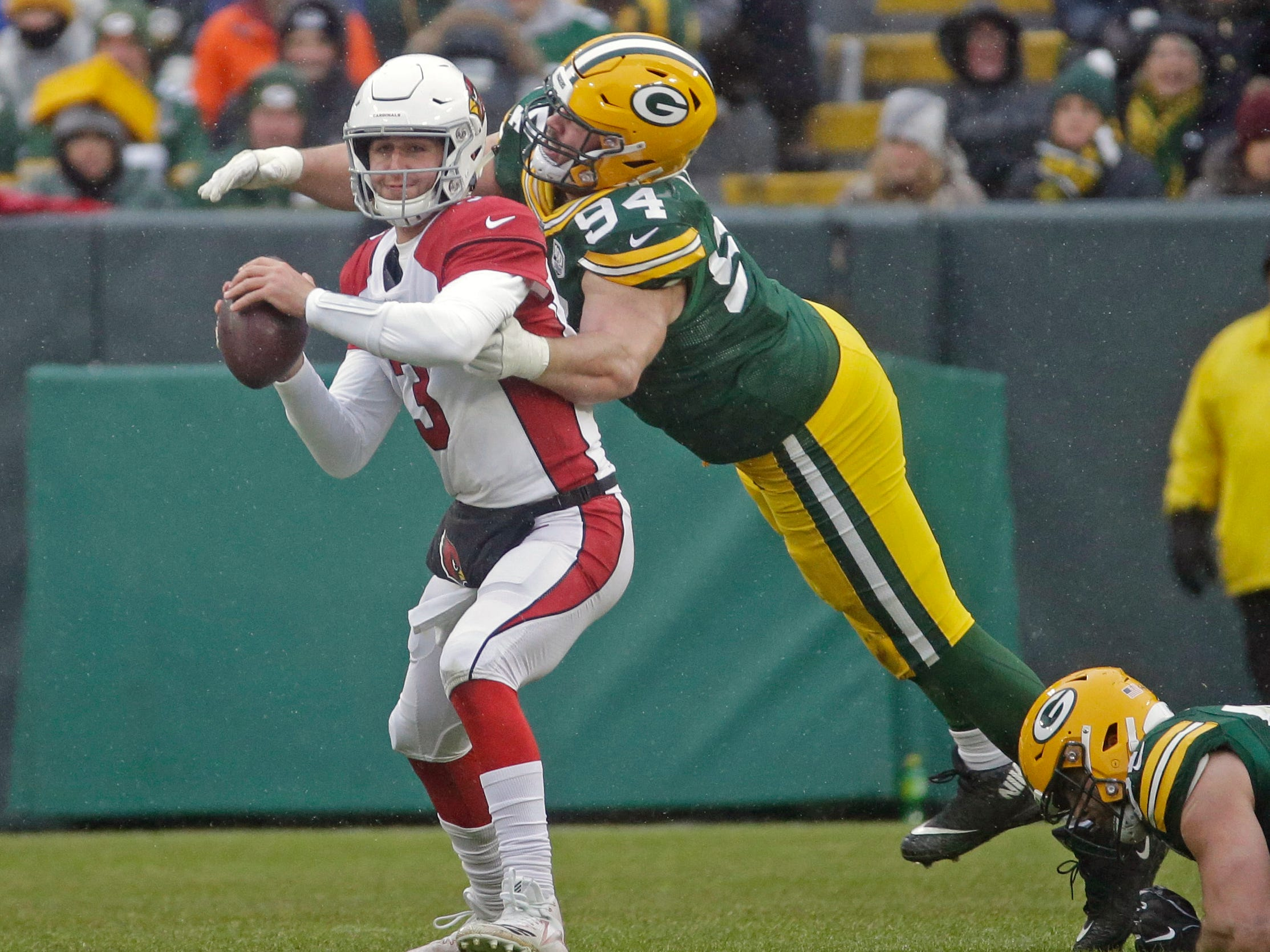 Arizona Cardinals quarterback Josh Rosen scrambles while being rushed by Green Bay Packers defensive end Dean Lowry during the second half of an NFL football game Sunday, Dec. 2, 2018, in Green Bay, Wis. (AP Photo/Mike Roemer)