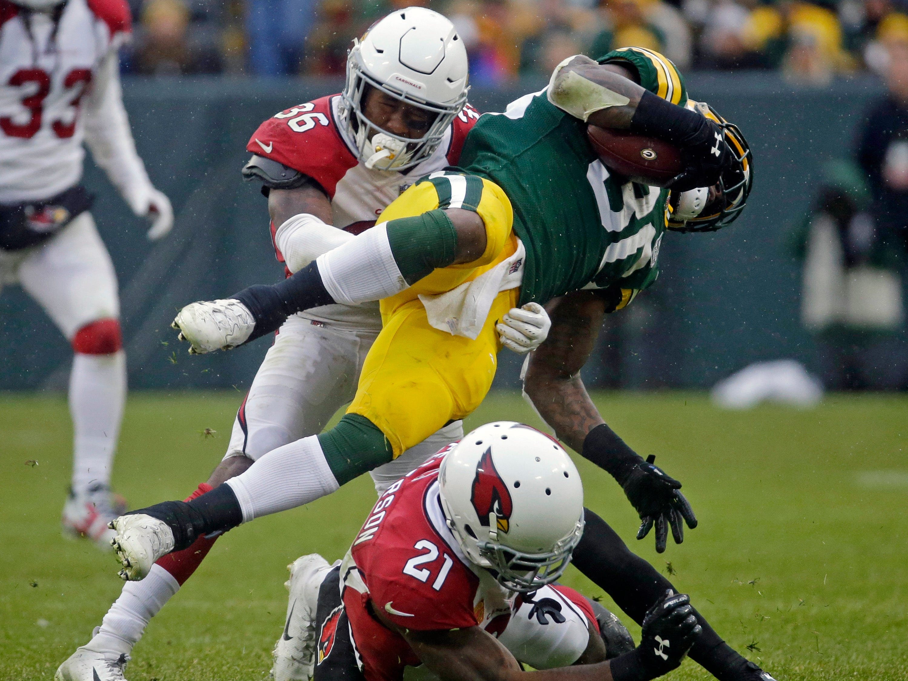Green Bay Packers running back Jamaal Williams (30) is hit during a run by Arizona Cardinals strong safety Budda Baker (36) and Patrick Peterson (21) during the second half of an NFL football game Sunday, Dec. 2, 2018, in Green Bay, Wis. (AP Photo/Mike Roemer)