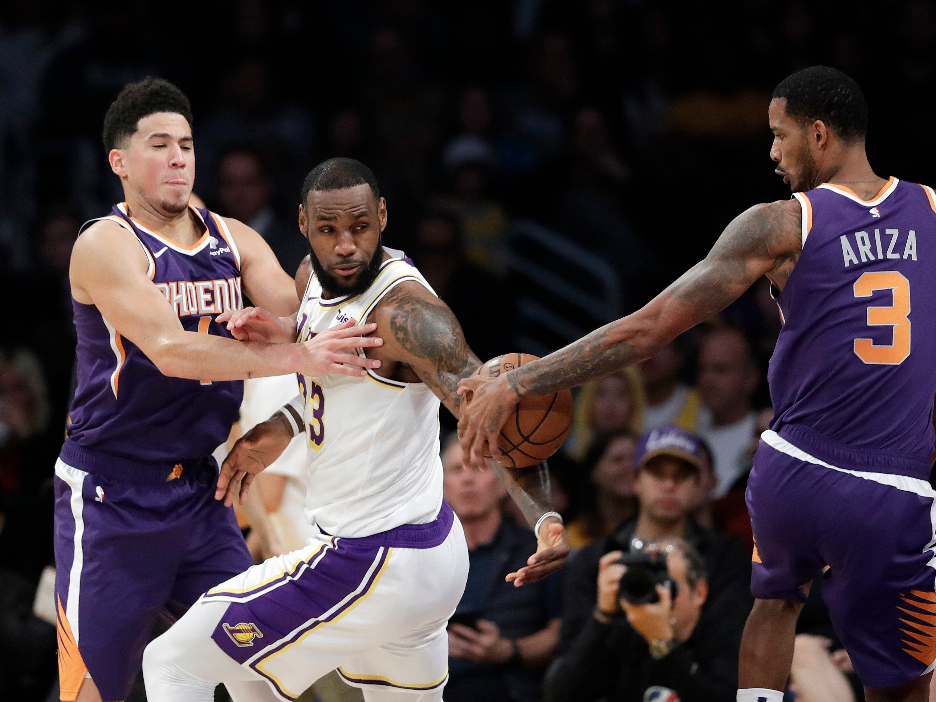 Phoenix Suns' Trevor Ariza (3) strips the ball from Los Angeles Lakers' LeBron James, center, during the first half of an NBA basketball game Sunday, Dec. 2, 2018, in Los Angeles. (AP Photo/Marcio Jose Sanchez)