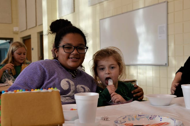 Jadyn Smith, 12 and Deziray Yax, 5, work on gingerbread houses at the Girl Scouts of Southeastern Michigan center on Dec. 2, 2018, in Port Huron, Michigan.