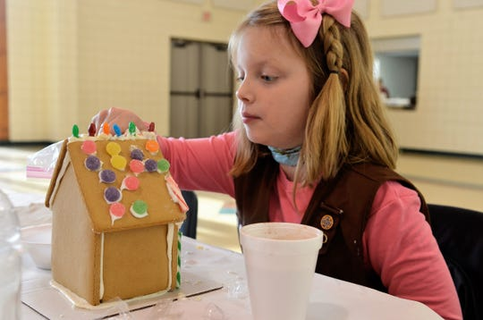 Girl scout Kennedi Fuller, 8, works on a gingerbread house at the Girl Scouts of Southeastern Michigan center on Dec. 2, 2018, in Port Huron, Michigan.