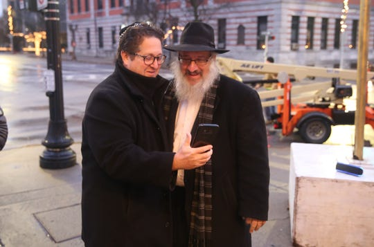 Jonah Ritter (left) and Rabbi Yacov Borenstein (right), both from Chabad of Mid-Hudson Valley, look at a photo on Ritter's phone during the first day of Hanukkah on Main Street in the City of Poughkeepsie. The organization plans to light a new candle each day until Dec. 10, the final day of Hanukkah.
