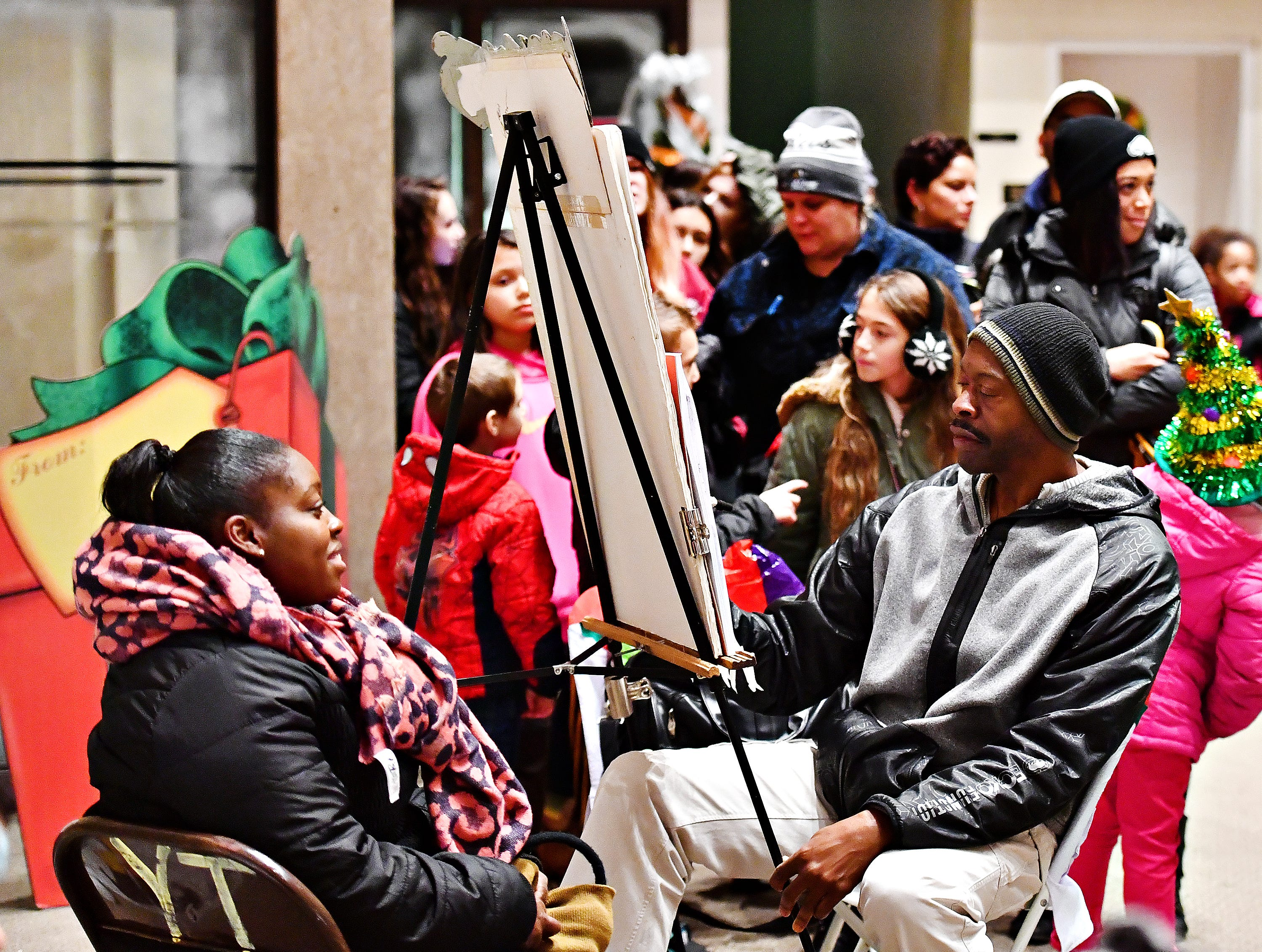 Francine Alston, left, of York City, sits while Artist Mel Conrad draws a caricature of her at the Photo Opp Stop during Light Up York in York City, Saturday, Dec. 1, 2018. Dawn J. Sagert photo