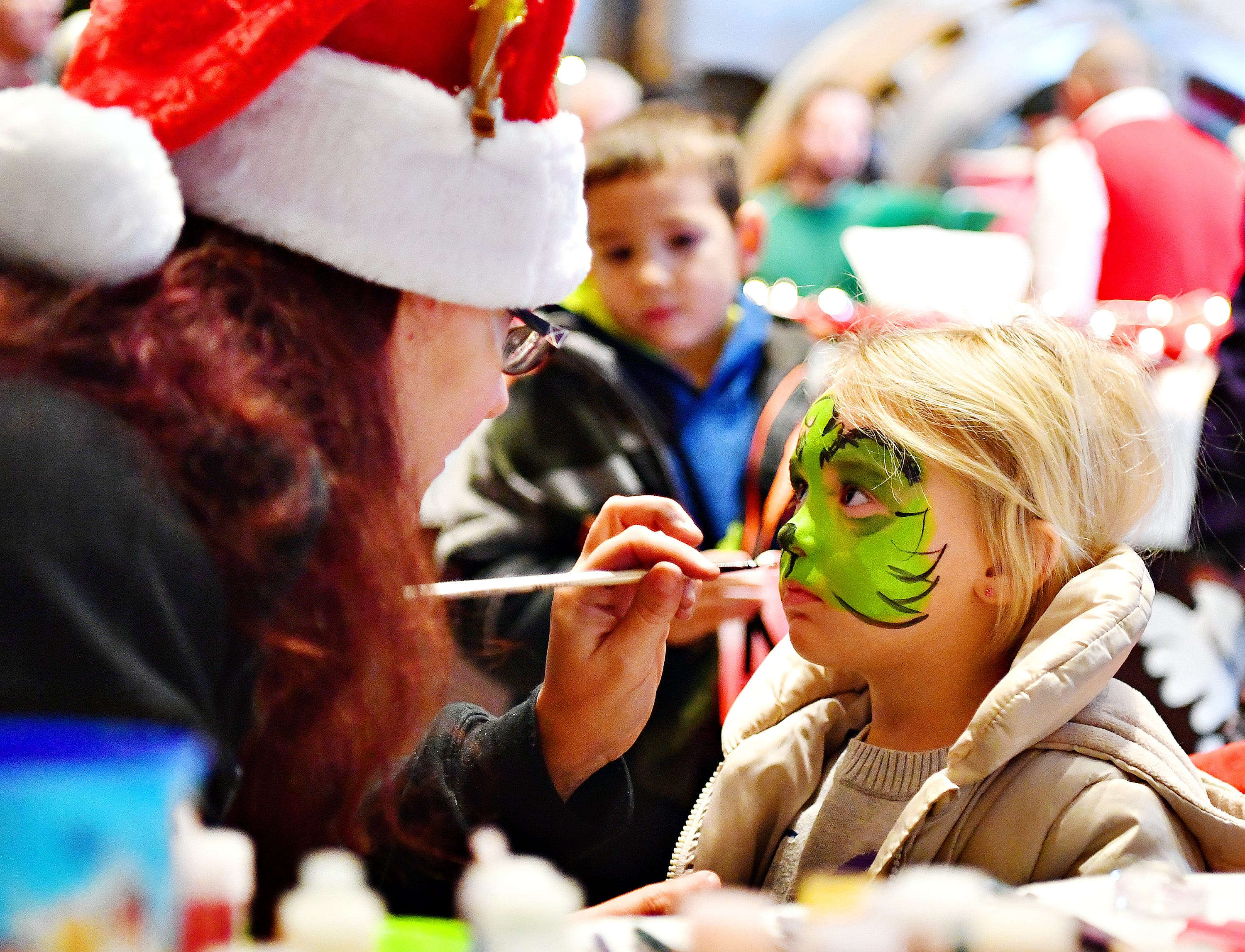 Katie Smock, left, of Atomic Bounce, paints a Grinch face on Avery Jackson, 3, right, of Springettsbury Township, while Carter Carroll, 6, of Springfield Township looks on at the Photo Opp Stop during Light Up York in York City, Saturday, Dec. 1, 2018. Dawn J. Sagert photo