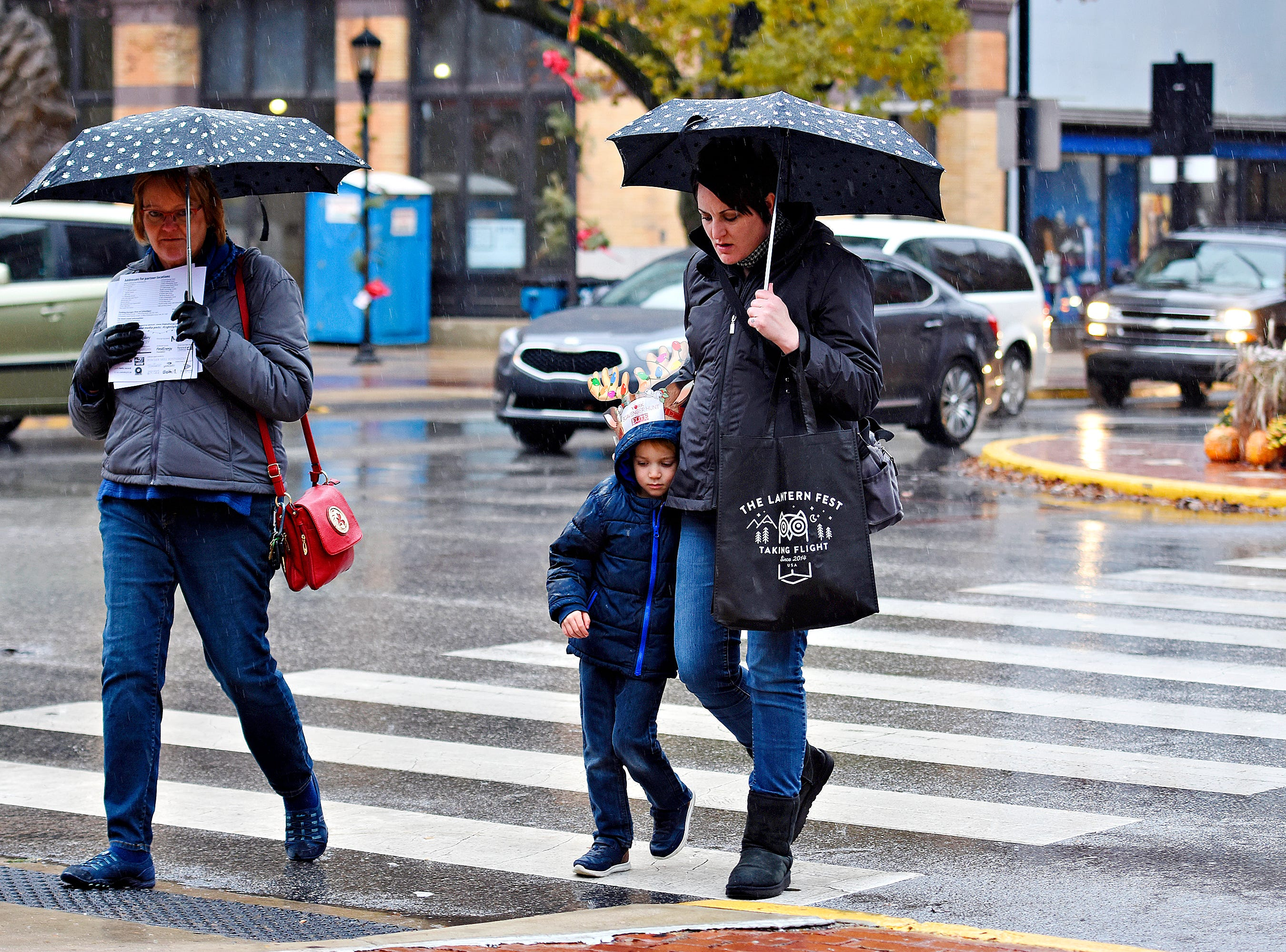 From left, Kathy Must, of Lower Windsor Township, Oliver Haines, 4, and his mother Melissa Musti, both of York City, cross George Street in the rain during Light Up York festivities in York City, Saturday, Dec. 1, 2018. Dawn J. Sagert photo