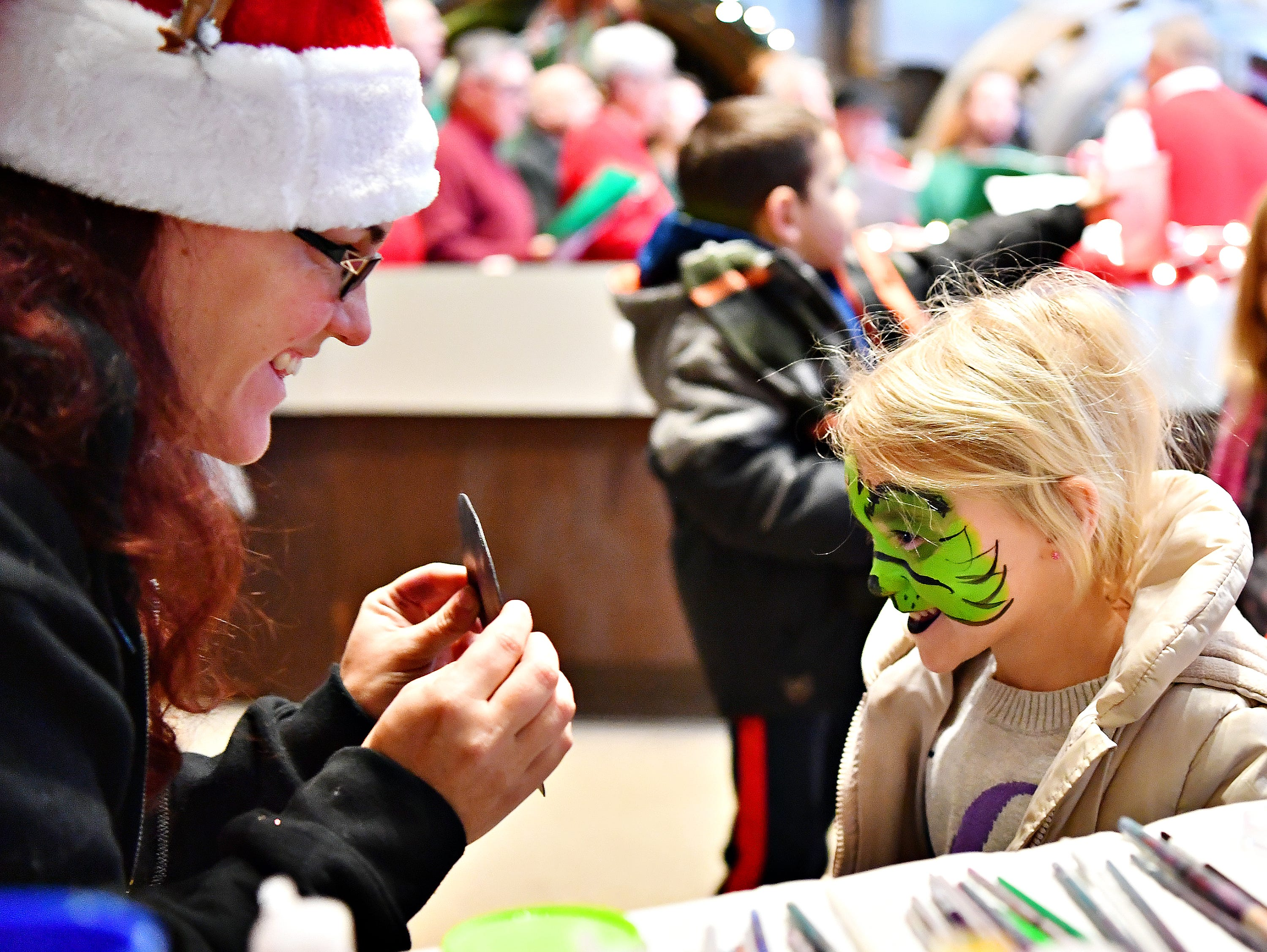Katie Smock, left, of Atomic Bounce, shows Avery Jackson, 3, right, of Springettsbury Township, her newly painted Grinch face in a mirror at the Photo Opp Stop during Light Up York in York City, Saturday, Dec. 1, 2018. Dawn J. Sagert photo