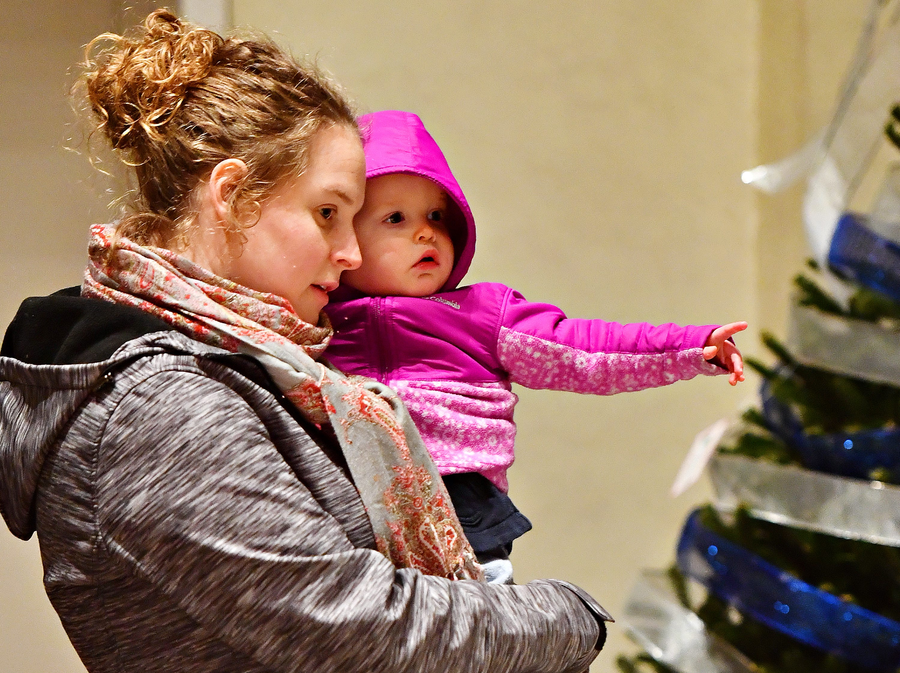 Kate Grady, of York City, holds her 17-month-old daughter Nora Grady as they watch musician Ian Carroll as he performs during Light Up York in York City, Saturday, Dec. 1, 2018. Dawn J. Sagert photo