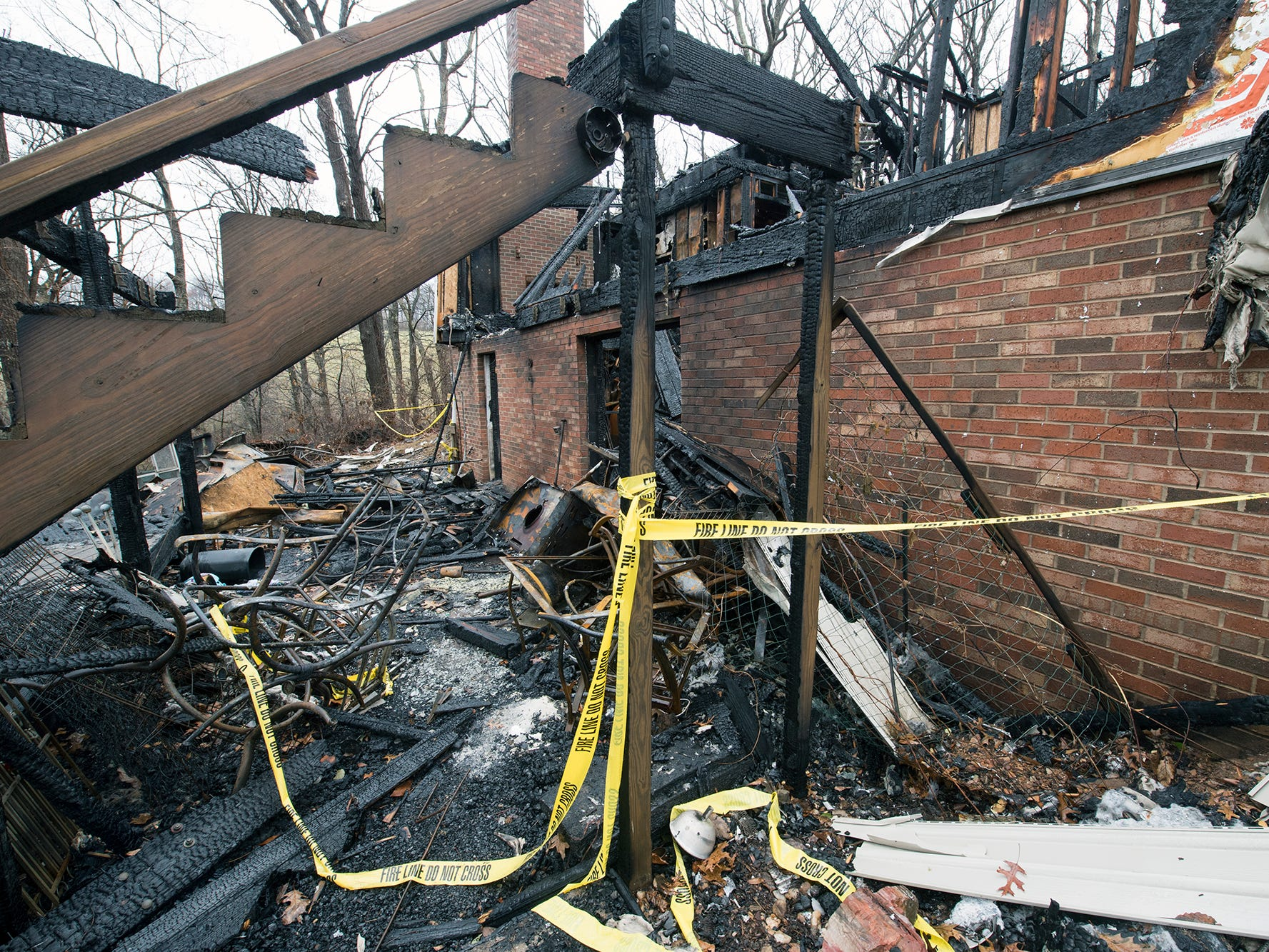 The deck on the back of the home is burned away from the brick foundation at the scene of the Shrewsbury Township fire on Sunday December 2, 2018.