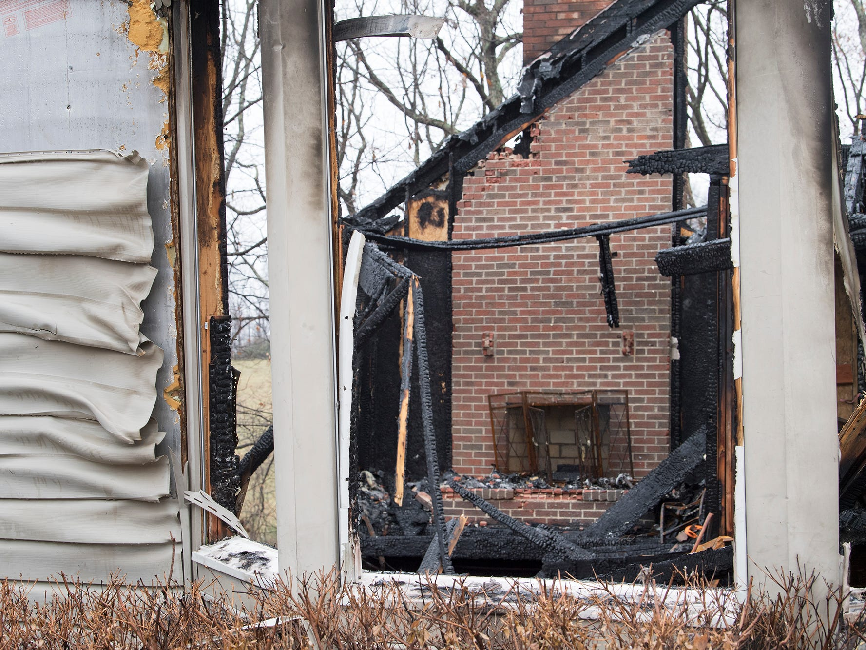 The fireplace where the fire began can be seen through a ground floor window at the scene of the Shrewsbury Township fire on Sunday December 2, 2018.