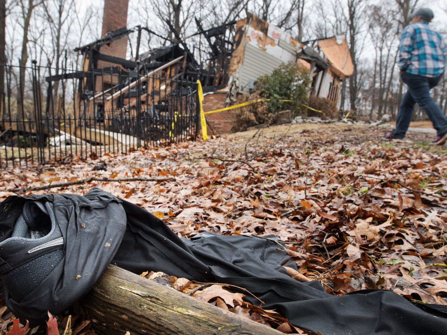 The burning clothing that Melissa Herren threw off in the early moments of the fire lies behind the house. Herring then ran to a farmhouse down the lane to call 911. Kyrstin Treaster, Herren's niece, walks toward the ruins on Sunday.