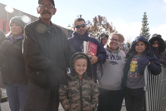 Reno resident Elizabeth Avila, 35, (middle) and her family watch the annual Sparks Hometowne Christmas Parade on Dec. 1, 2018 at Victorian Square.