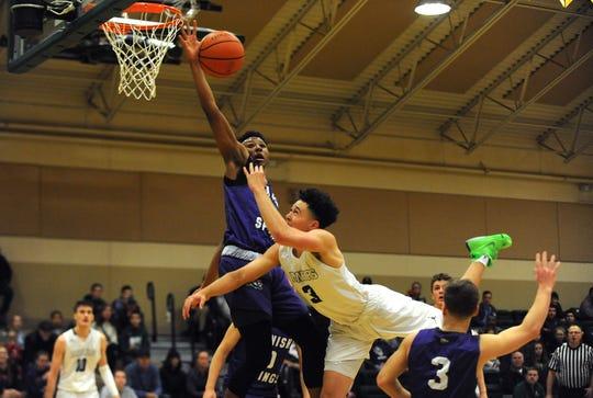 Spanish Springs' Cordell Stinson blocks the shot of Bishop Manogue's Dan Bansuelo during their Wild West Shootout basketball game at Bishop Manogue in Reno on Dec. 1.