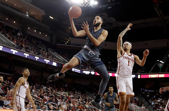 Nevada's Caleb Martin, center, drives past Southern California's Jordan Usher during the second half of Saturday's game in Los Angeles.