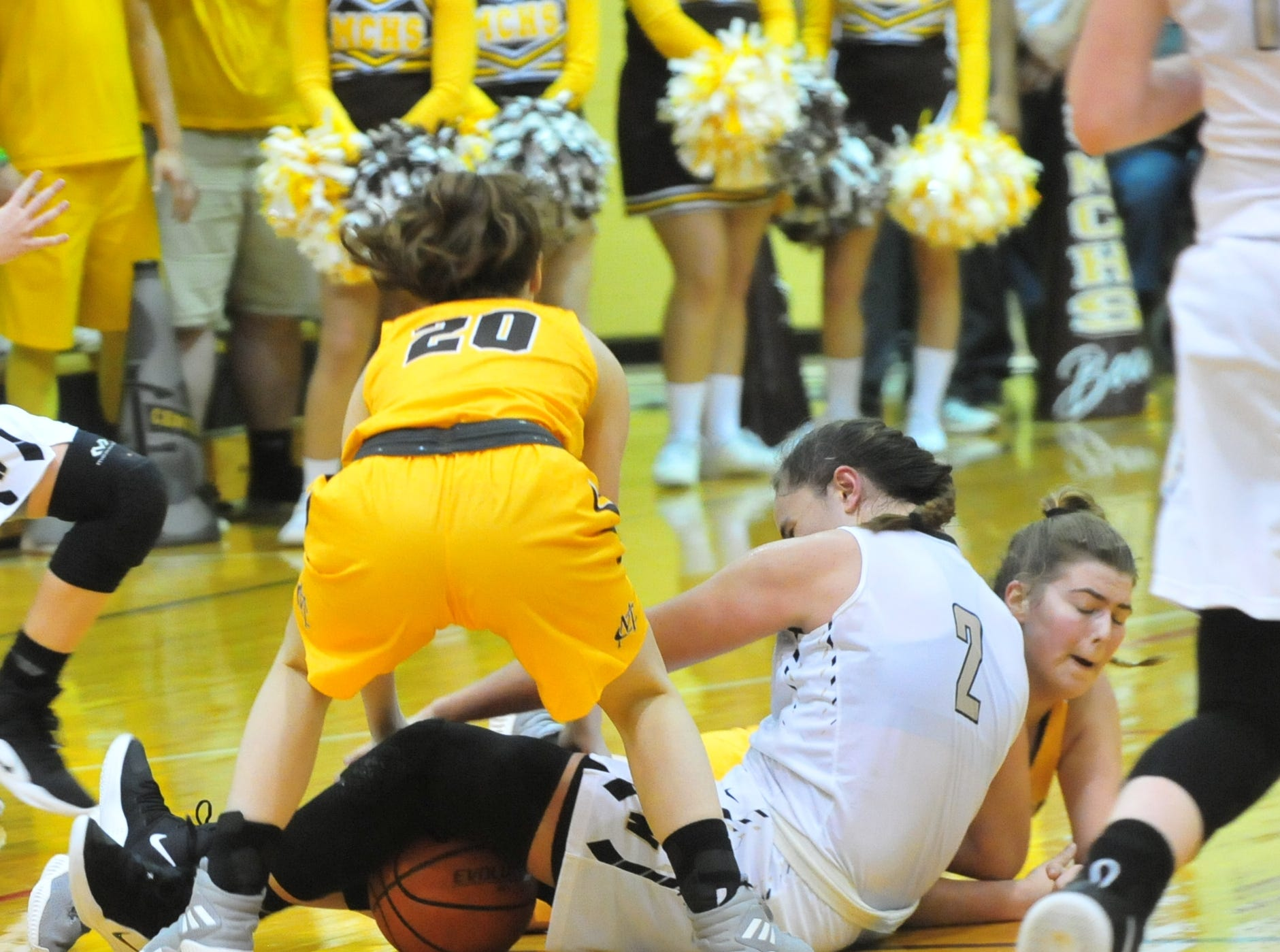 Winchester's Maddie Lawrence (2) battles a pair of Monroe Central players for a loose ball during Winchester's 64-39 girls basketball win over Monroe Central Saturday, Dec. 1, 2018 at Winchester Fieldhouse.
