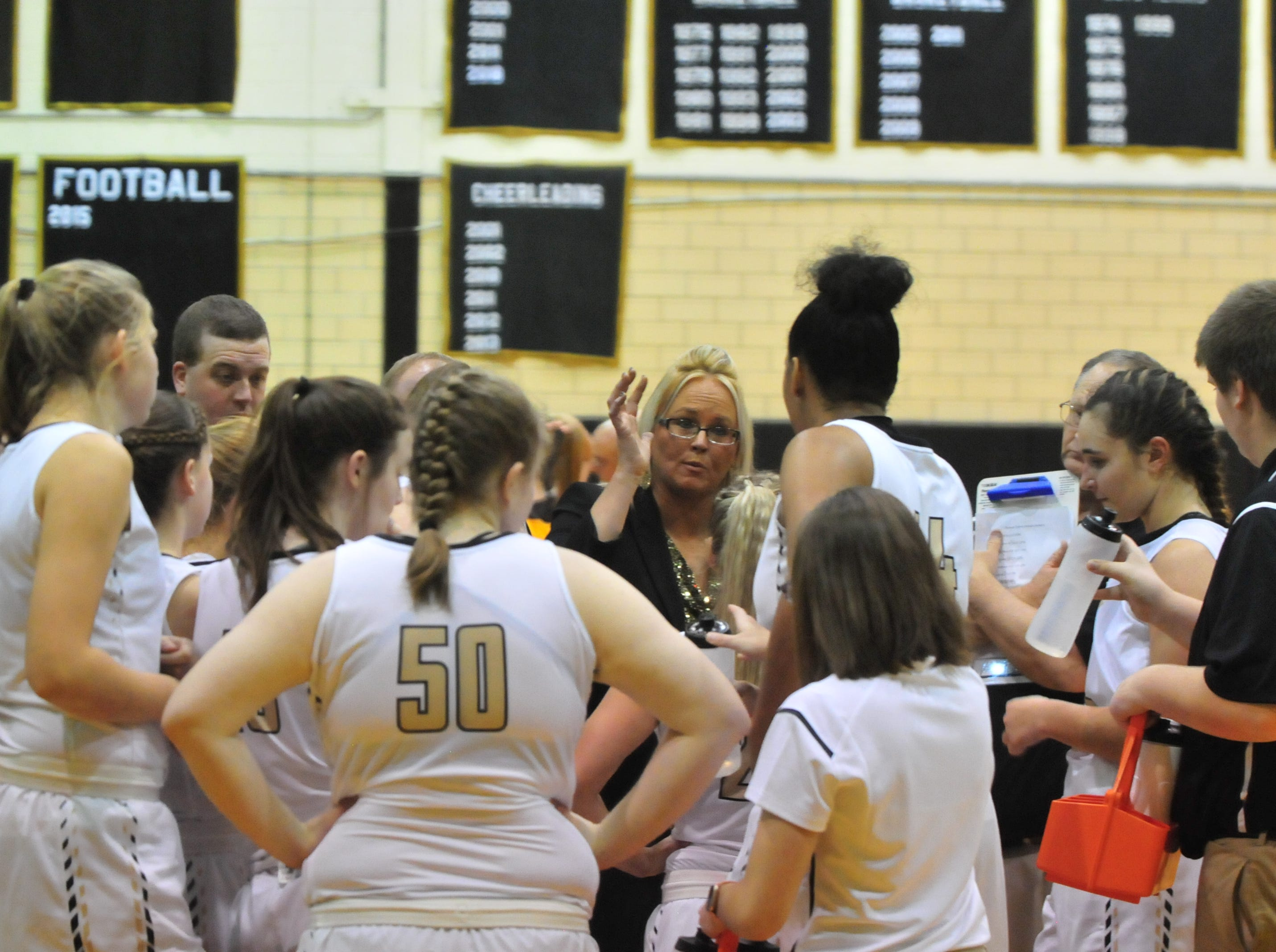 Winchester head coach Holly Gutierrez addresses her team during Winchester's 64-39 girls basketball win over Monroe Central Saturday, Dec. 1, 2018 at Winchester Fieldhouse.