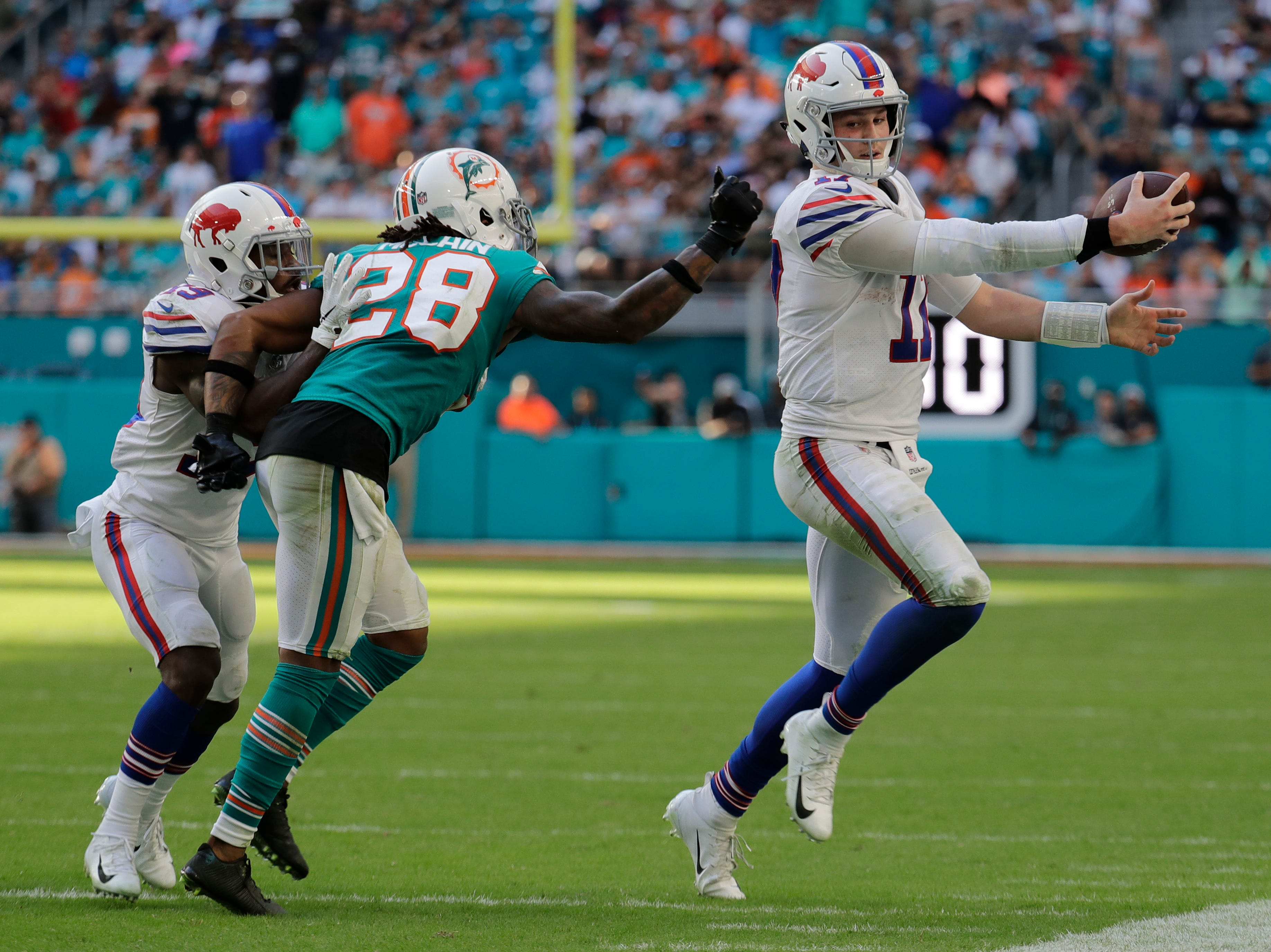 Buffalo Bills quarterback Josh Allen (17) runs the ball as Miami Dolphins cornerback Bobby McCain (28) attempts to tackle, during the second half of an NFL football game, Sunday, Dec. 2, 2018, in Miami Gardens, Fla. (AP Photo/Lynne Sladky)