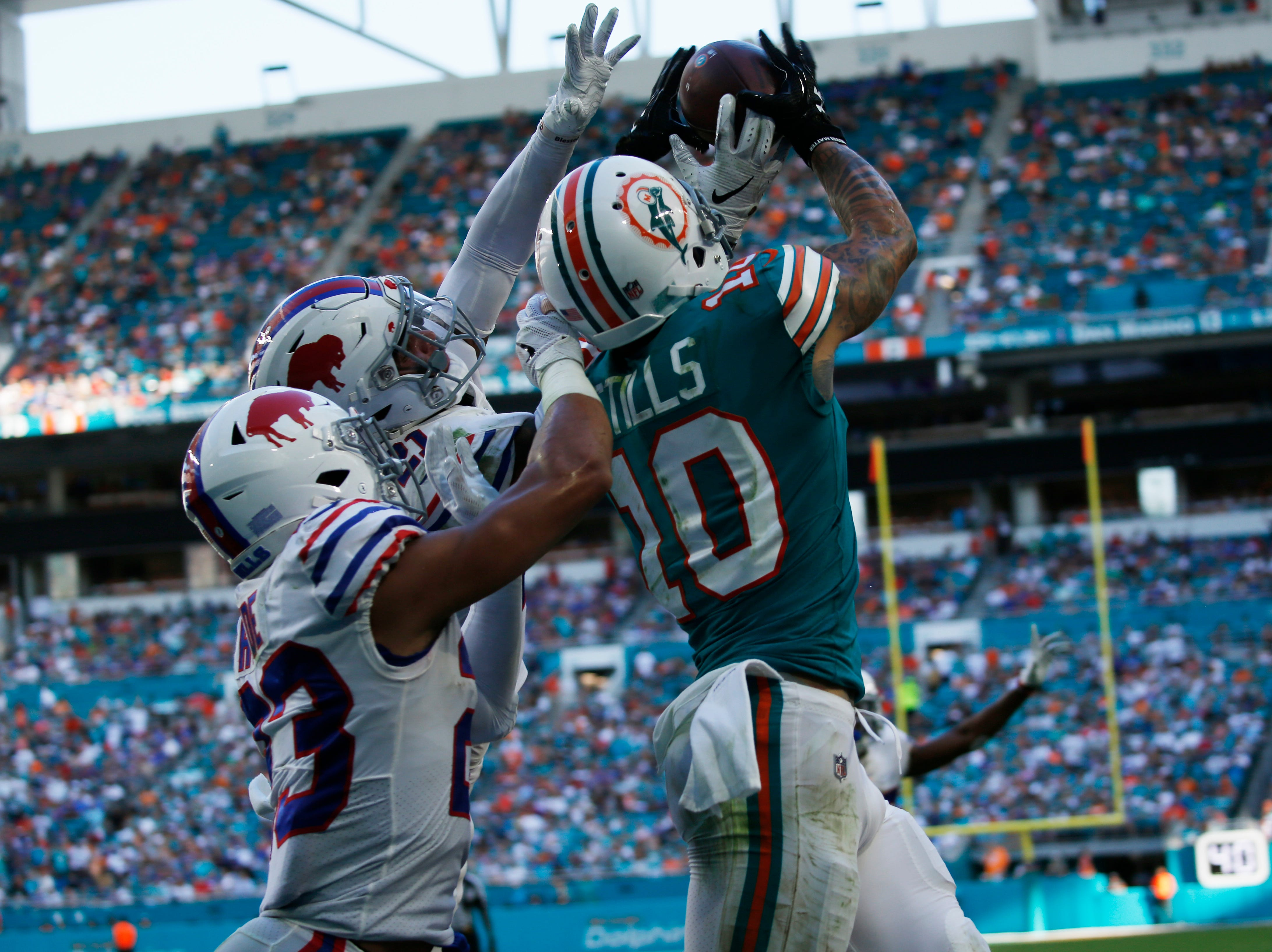 Miami Dolphins wide receiver Kenny Stills (10), catches a touchdown as Buffalo Bills free safety Jordan Poyer (21) and strong safety Micah Hyde (23) defend, during the second half of an NFL football game, Sunday, Dec. 2, 2018, in Miami Gardens, Fla. (AP Photo/Joel Auerbach)