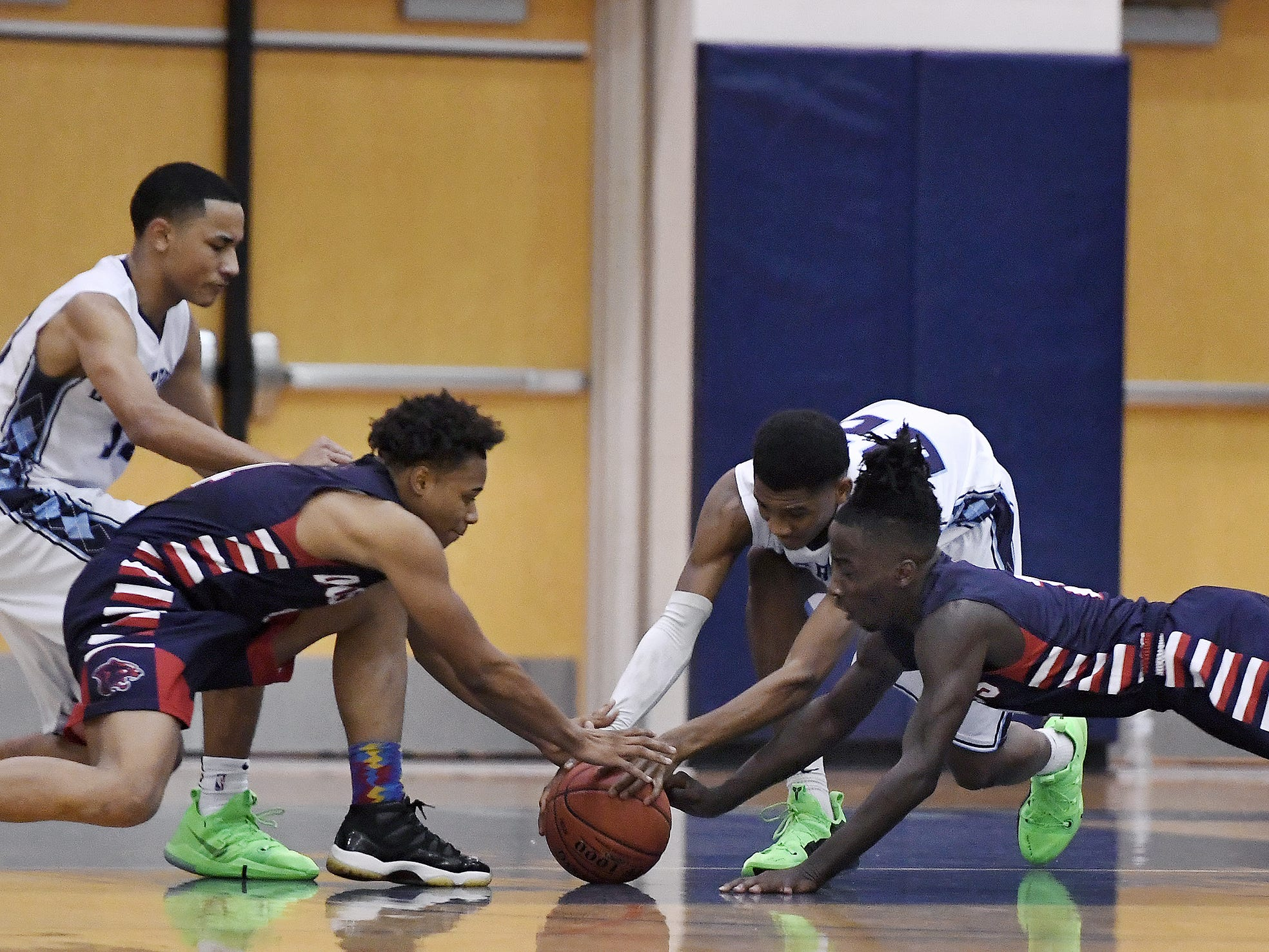 NE Douglass' Trevion Miller, left, and Jiahmere Mitchell dive for a loose ball against Eastridge's Jahmel Demery during the finals of the Al Masino Memorial Tip-Off Tournament.