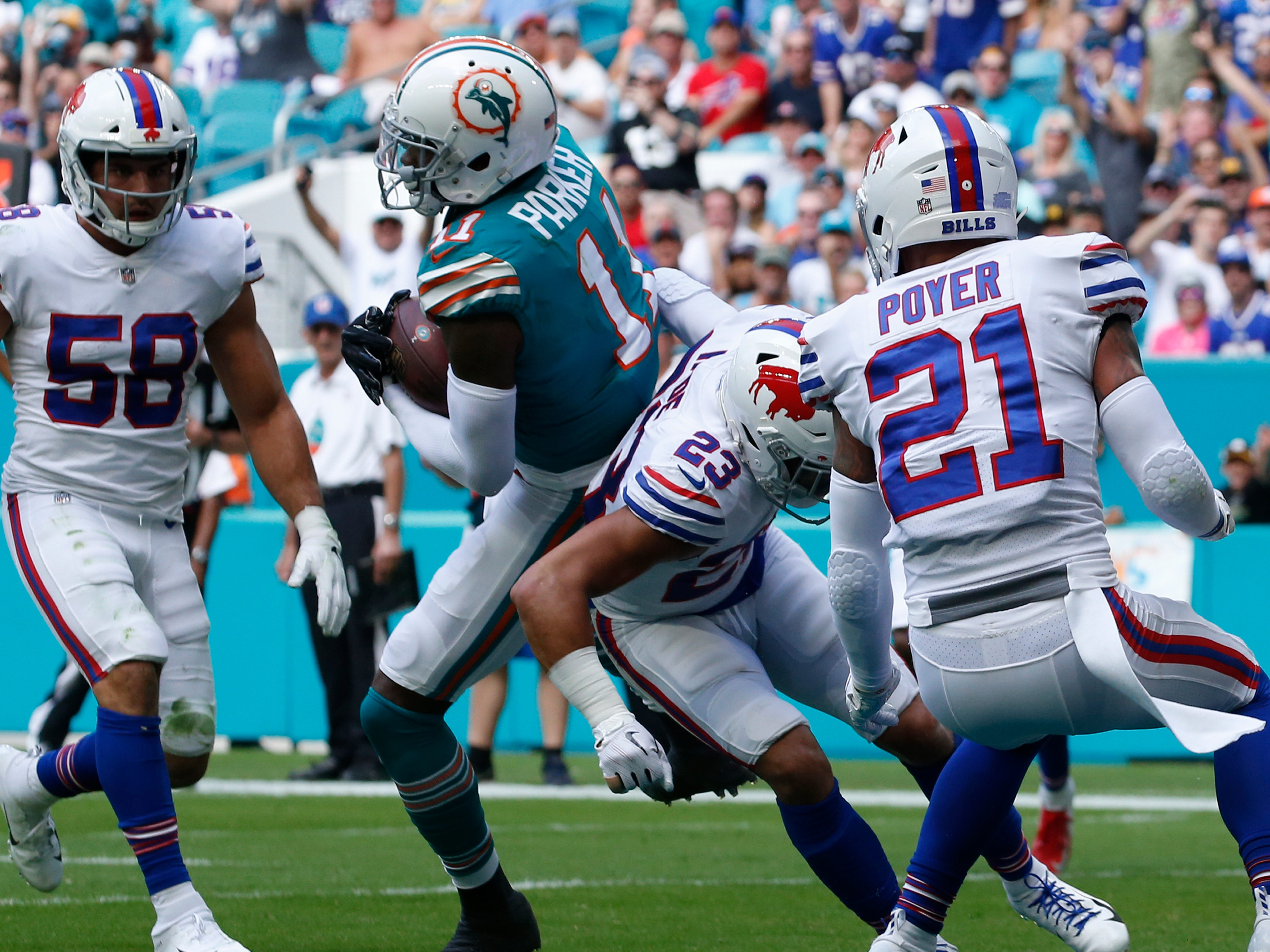 Miami Dolphins wide receiver DeVante Parker (11) catches a pass for a touchdown over Buffalo Bills strong safeties Micah Hyde (23) and Jordan Poyer (21), during the first half of an NFL football game, Sunday, Dec. 2, 2018, in Miami Gardens, Fla. To the left is Buffalo Bills outside linebacker Matt Milano (58). (AP Photo/Joel Auerbach)