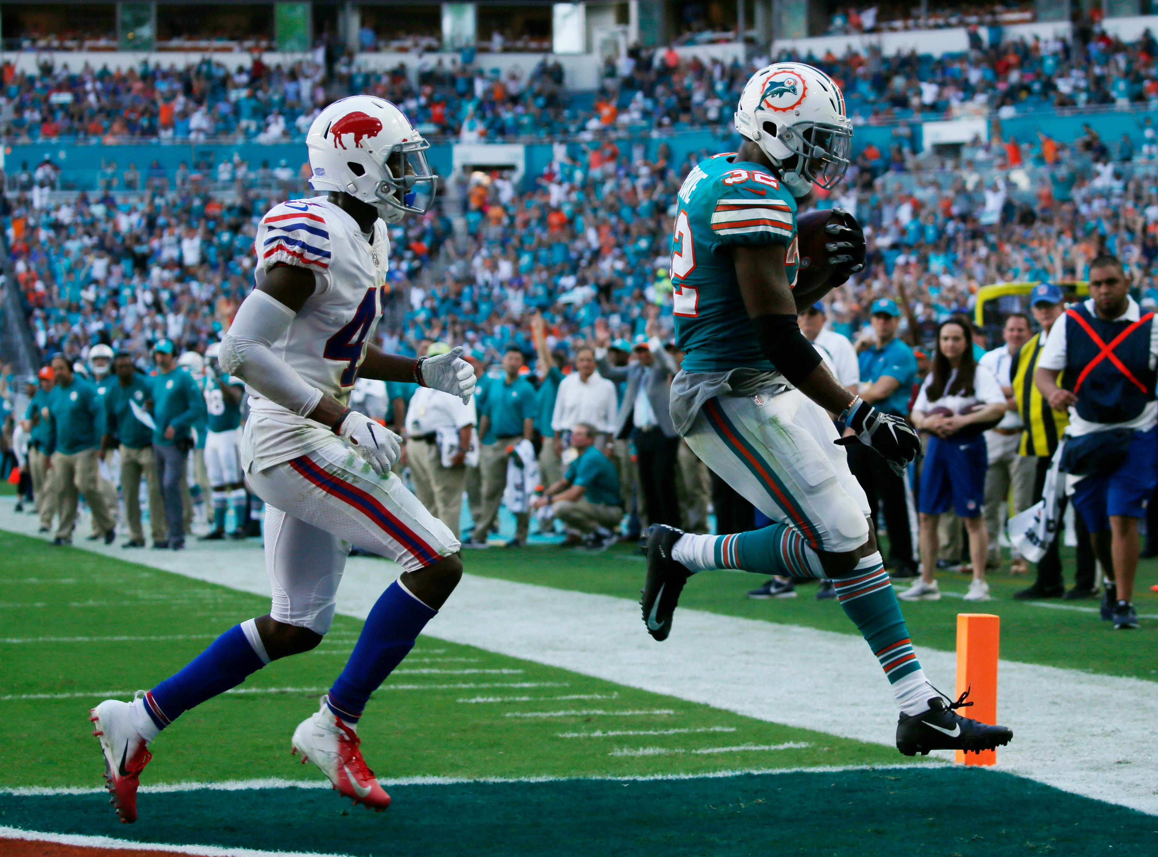 Miami Dolphins running back Kenyan Drake (32) runs for a touchdown ahead of Buffalo Bills defensive back Levi Wallace (47), during the first half of an NFL football game, Sunday, Dec. 2, 2018, in Miami Gardens, Fla. (AP Photo/Joel Auerbach)