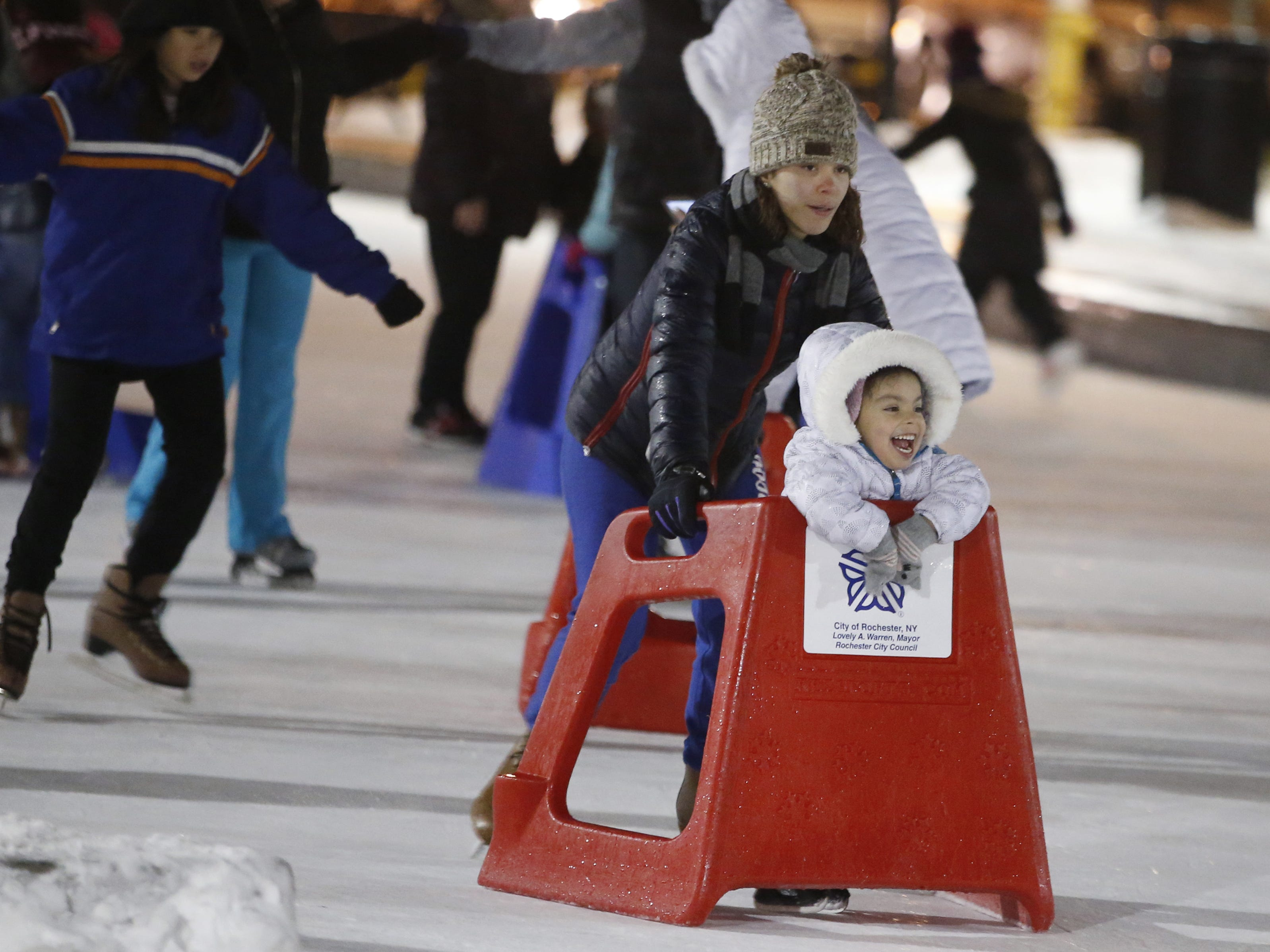 Madailee Rivera of Rochester pushes her daughter Natalee, 4, at Dr. Martin Luther King, Jr. Memorial Park ice skating rink during the ROC Holiday Village event.