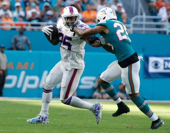 Miami Dolphins cornerback Xavien Howard (25) grabs the facemark of Buffalo Bills running back LeSean McCoy (25), during the second half of an NFL football game, Sunday, Dec. 2, 2018, in Miami Gardens, Fla. (AP Photo/Joel Auerbach)