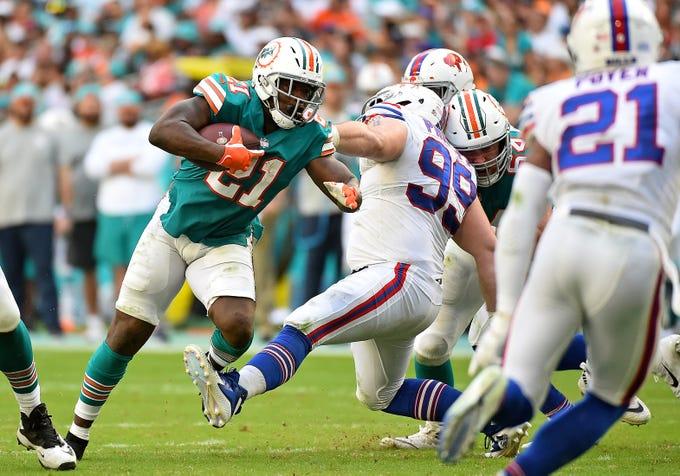 Dec 2, 2018; Miami Gardens, FL, USA; Buffalo Bills defensive tackle Harrison Phillips (99) trips Miami Dolphins running back Frank Gore (21) during the first half at Hard Rock Stadium. Mandatory Credit: Jasen Vinlove-USA TODAY Sports