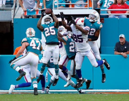 Miami Dolphins cornerback Xavien Howard (25) intercepts a long pass in the enzone intended for Buffalo Bills tight end Charles Clay (85), during the first half of an NFL football game, Sunday, Dec. 2, 2018, in Miami Gardens, Fla. (AP Photo/Joel Auerbach)