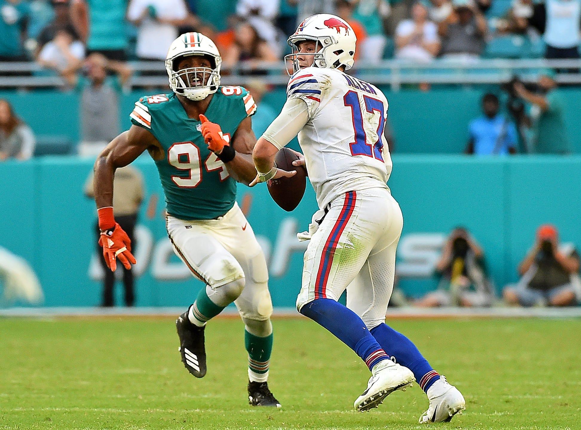 Buffalo Bills quarterback Josh Allen (17) attempts a pass under pressure from Miami Dolphins defensive end Robert Quinn (94) during the second half at Hard Rock Stadium.