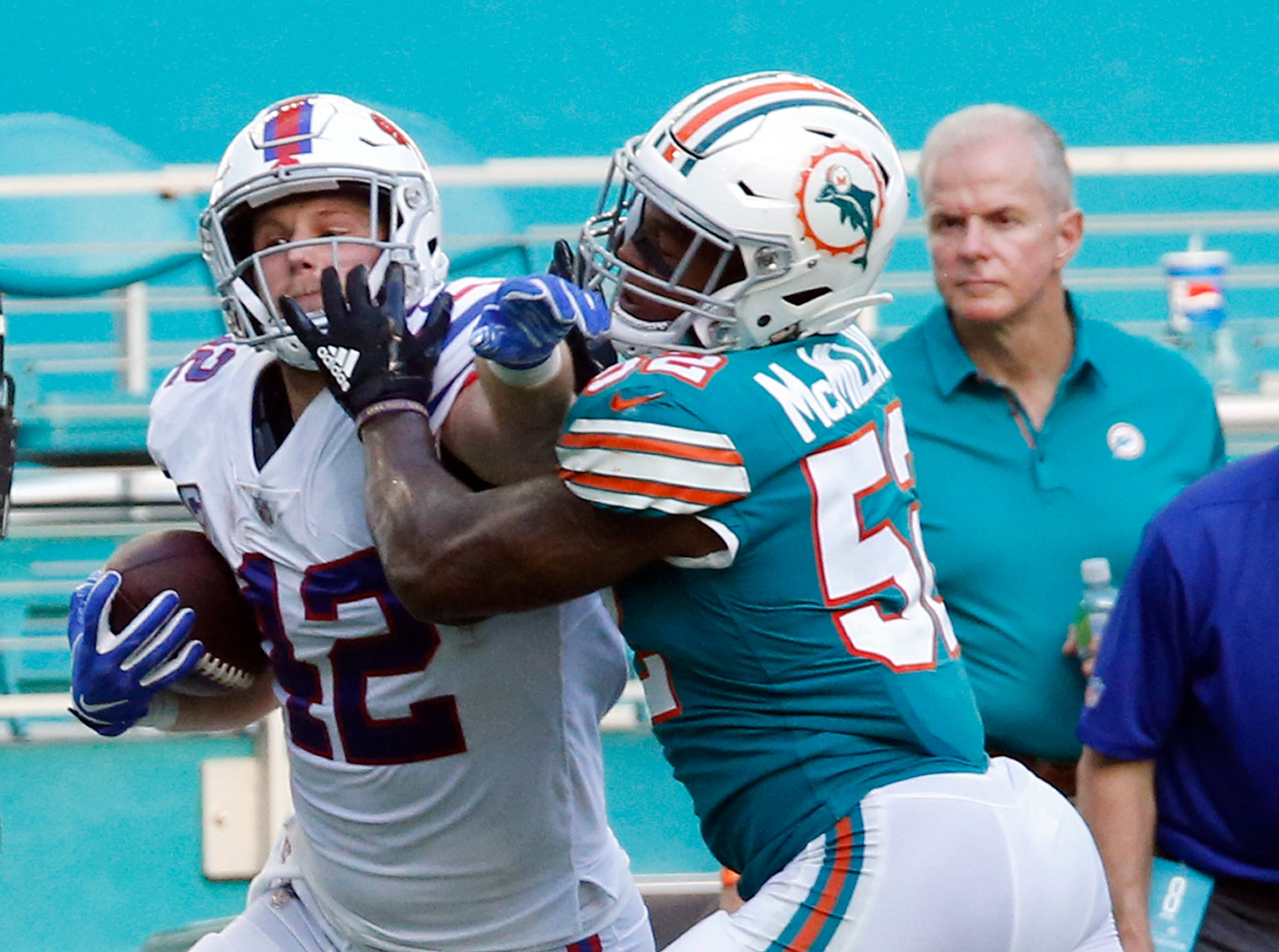 Miami Dolphins middle linebacker Raekwon McMillan (52) grabs Buffalo Bills running back Patrick DiMarco (42), during the second half of an NFL football game, Sunday, Dec. 2, 2018, in Miami Gardens, Fla. (AP Photo/Joel Auerbach)