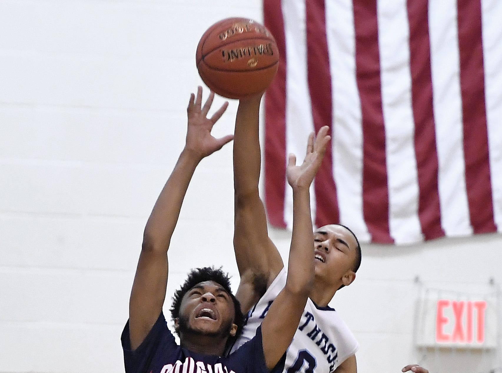NE Douglass' Nicolas Jeanty (5) and Eastridge's Jaden Keech reach for a rebound during the finals of the Al Masino Memorial Tip-Off Tournament.