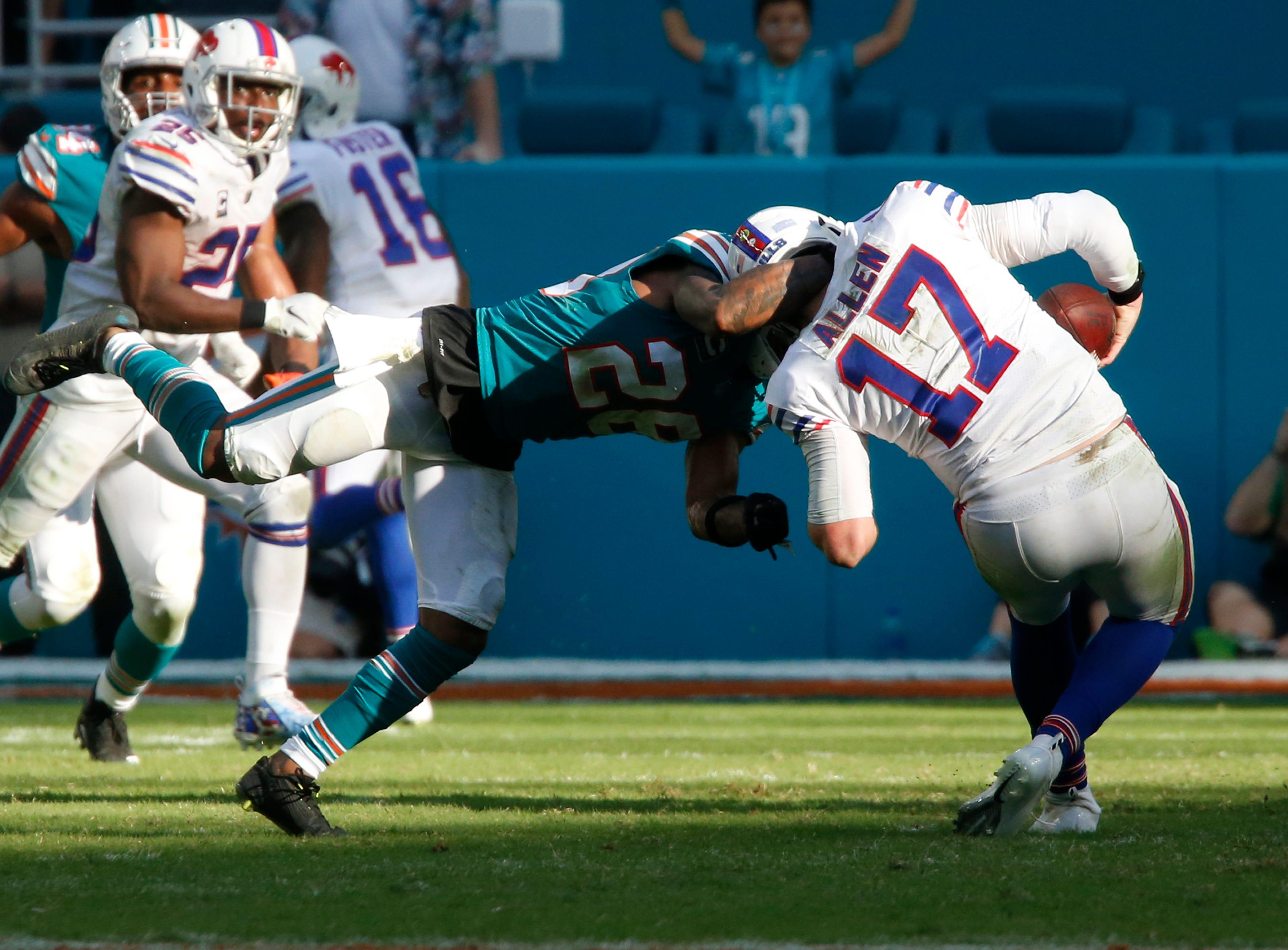 Miami Dolphins cornerback Bobby McCain (28) sacks Buffalo Bills quarterback Josh Allen (17), during the second half of an NFL football game, Sunday, Dec. 2, 2018, in Miami Gardens, Fla. The Dolphins defeated the Bills 21-17. (AP Photo/Joel Auerbach)