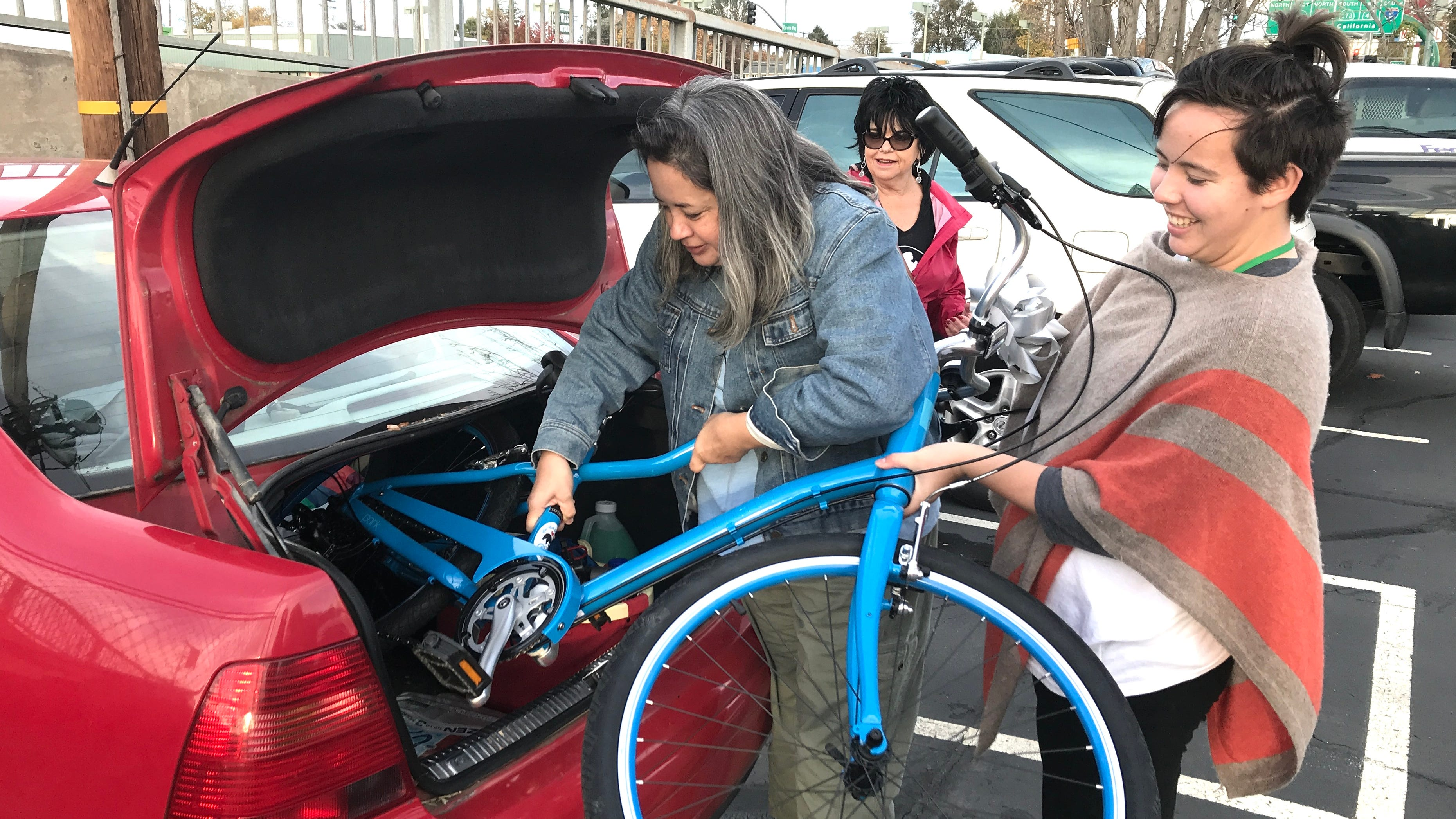 Hilly Wallis, left, gets help from her daughter, Ella Wallis, right, in loading her new bicycle Saturday courtesy of Giant Bicycles. The Chain Gang Bike Shop hosted a gifting party where 50 adult survivors of the Carr Fire received the free bikes, valued at $500.