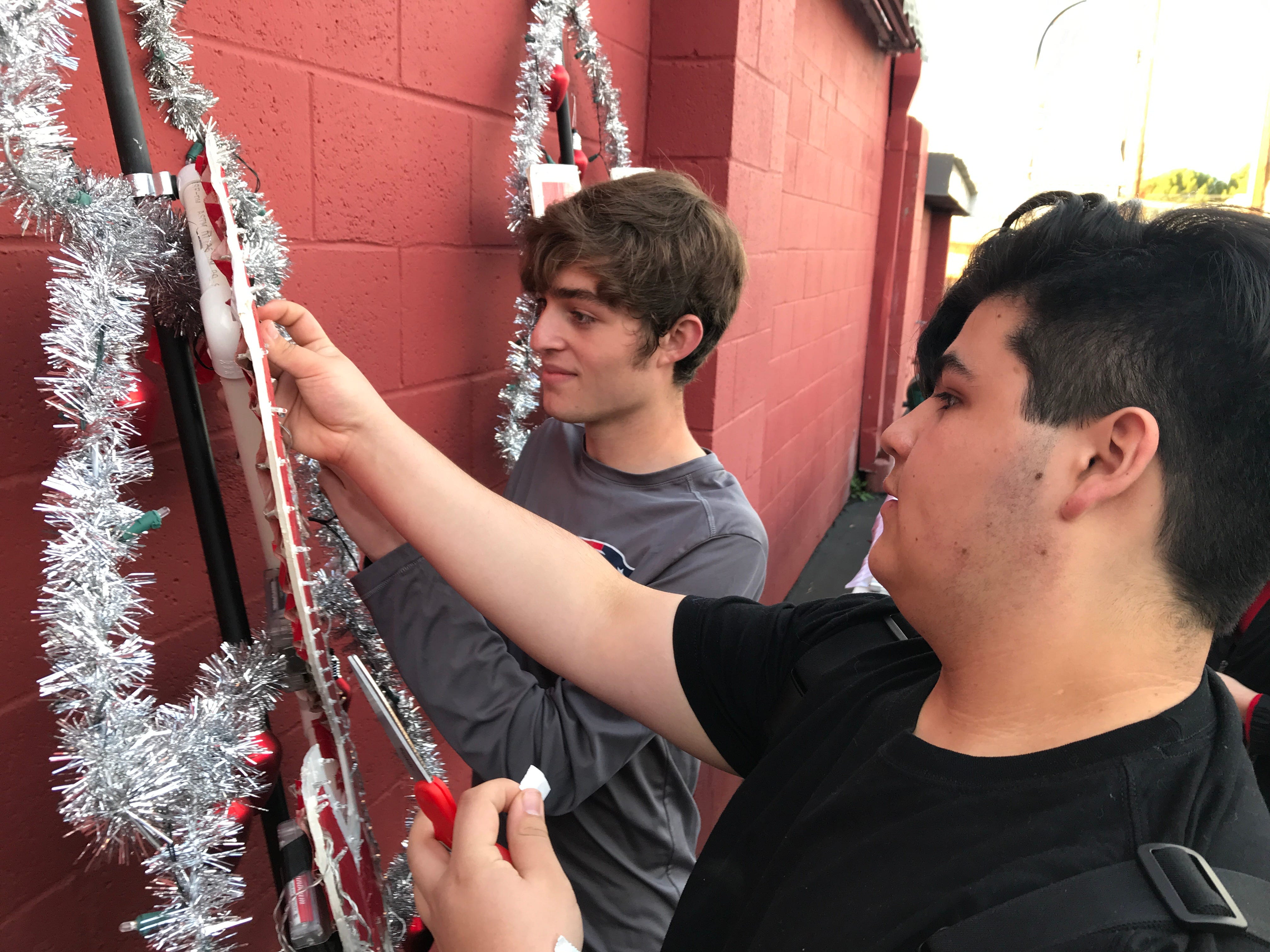 Foothill High School seniors Jarred Lessinger, left, and Joshua Varela prepare their school's float Saturday before the sun went down for the annual Lighted Christmas parade in downtown Redding.