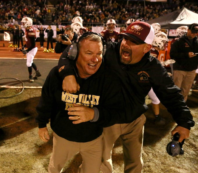 Head coach Greg Grandell, left, celebrates on the sideline after the Eagles beat the Sutter Huskies, 7-0, at home to win the Division III Northern Section championship on Saturday, Dec. 1.