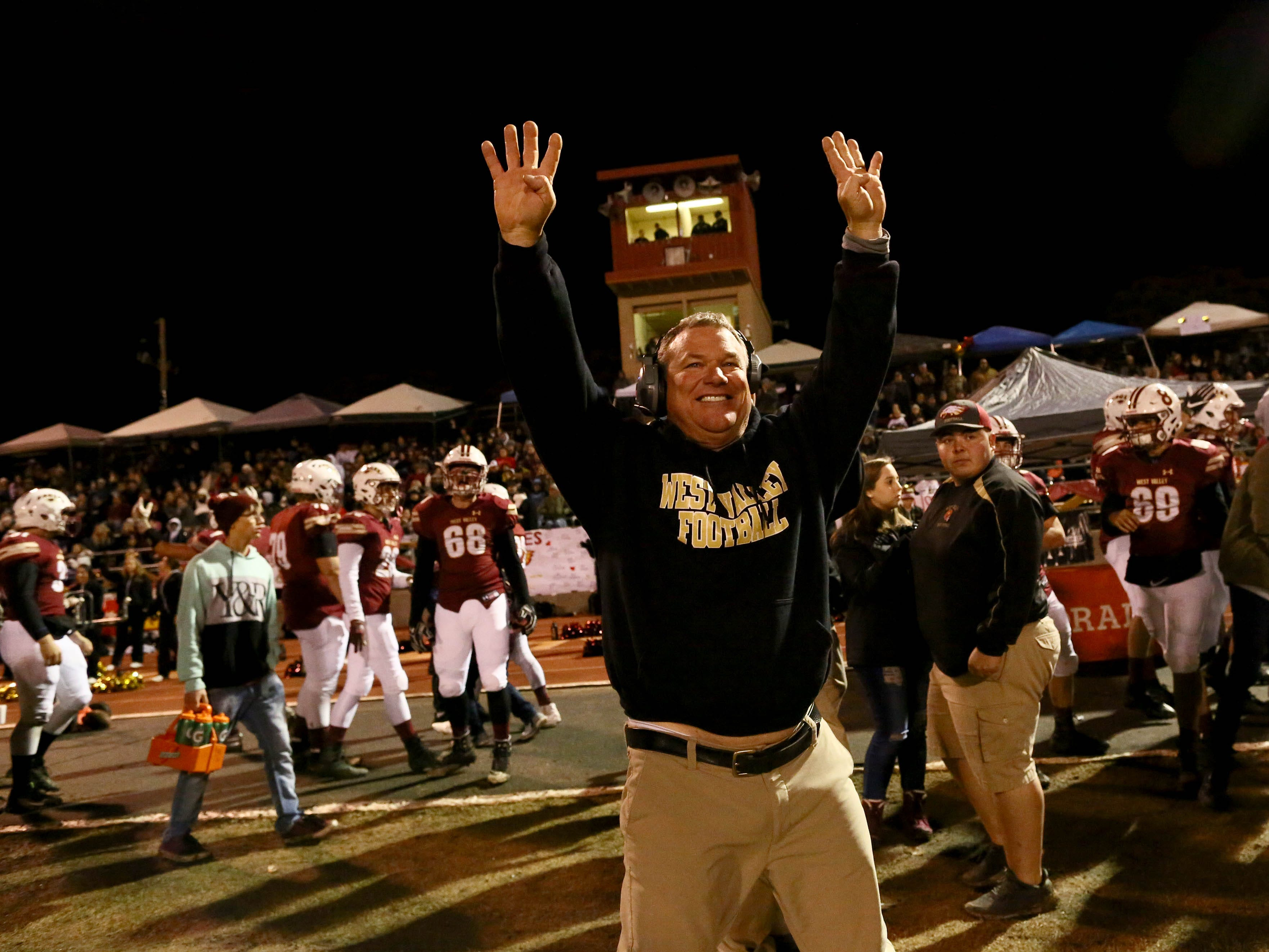 West Valley head coach Greg Grandell holds up eight fingers in honor of Tyson Wacker as the Eagles beat the Sutter Huskies, 7-0 , to take the Division III Northern Section championship in Cottonwood on Saturday, Dec. 1.